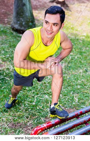 Asian man stretching in fitness exercise or sport training in tropical park