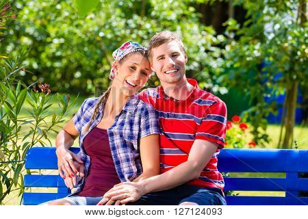 Man and woman in garden sitting on bench