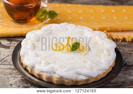 lemon tart on a plate decorated with lemons