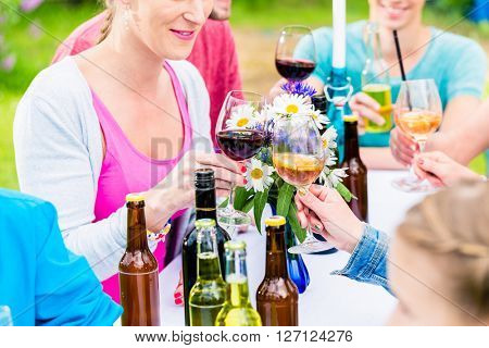 Friends celebrating small garden party clinking glasses