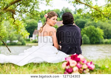 Wedding couple of bride and groom sitting on the meadow at river with bridal bouquet behind them