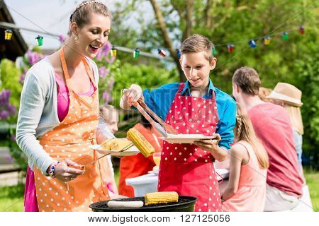 Mother and son grilling meat at garden barbeque
