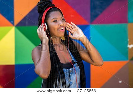 Afro woman listing to music on colorful background