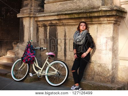 Girl with a vintage bicycle on a background of a wall of an ancient building