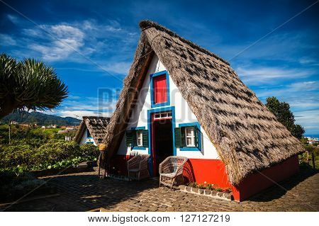 traditional small-thatched triangular Madeira house built of wood and thatched with straw