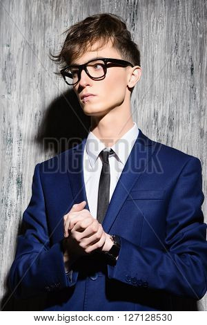 Young stylish man with fashionable haircut wearing elegant suit and spectacles.