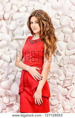 Beautiful girl in red dress posing by a background of white paper flowers. Spring  and summer concept. Fashion shot.