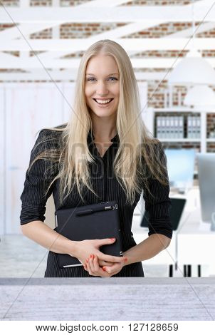 Portrait of happy smiling young nordic businesswoman holding tablet, looking at camera.