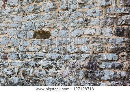 Empty gray stone wall covered with cracks of old house. Urban background grunge. Beauty world.