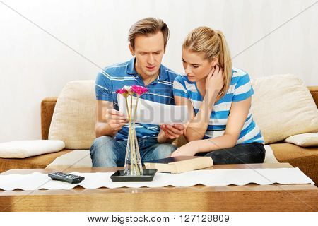 Young couple examining plans of apartment