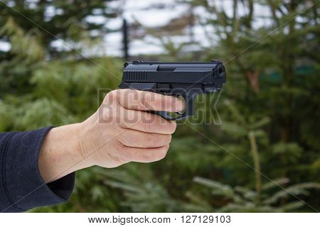 Woman shooting outdoor with a gun selective focus after shoot the Pistol.