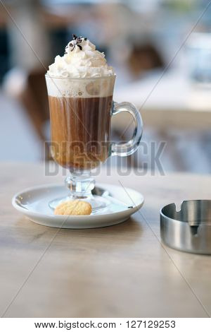 Latte with whipped cream in outdoor restaurant