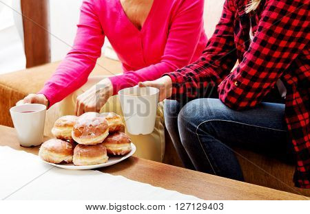 Mother and daughter sitting on couch with donuts and tea on table