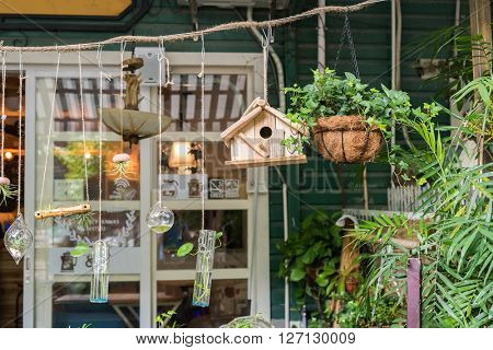 cafe with birdhouse nestles,glass bottle,flower