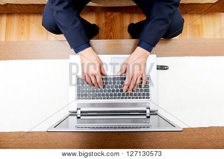 Aerial view of man's hands on laptop