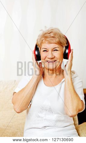 Happy senior woman wearing red headphones