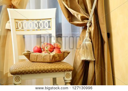 chair with a basket of apples near a curtain with a holding strap