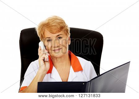 Smile elderly female doctor or nurse sitting behind the desk and talking through a phone