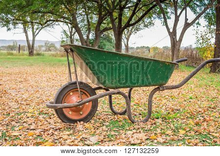 Photo of used old wheelbarrow in a farm yard