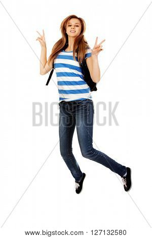 Teenage woman with backpack jumping and gesturing peace