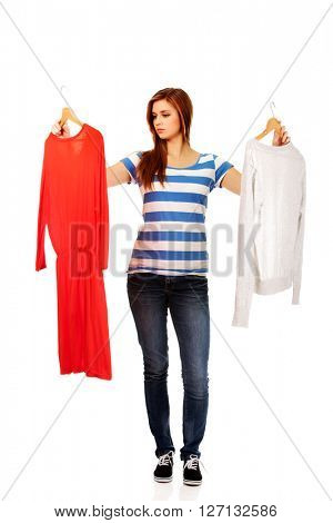 Teenage woman with two shirts thinking what to dress