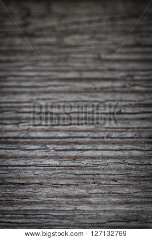 Old weathered wooden background with horizontal cracked. Close up of gray odl plank with slots.