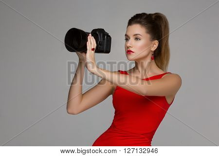 Beautiful photographer woman holding dslr camera with portrait lense. Over grey background. Copy space.