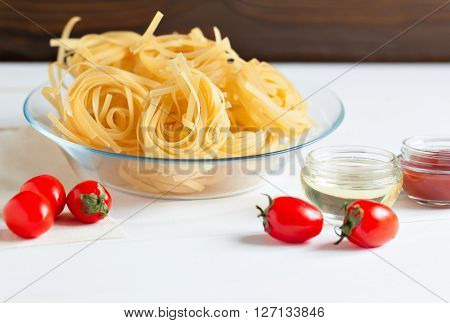 Two kinds of pasta from durum wheat and fresh tomatoes for making the sauce. Products on a wooden table.