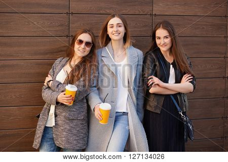 three young stylish woman outdoors