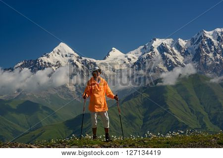 Tourist dressed in orange jacket against mountains covered with snow background. Alpine meadow with white flowers in foreground.