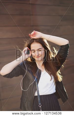 Young beautiful hipster woman listening music with headphones in the city.