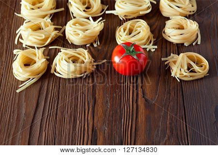 Products on a wooden table with copy space. pasta from durum wheat and fresh tomatoes, tomato sauce.