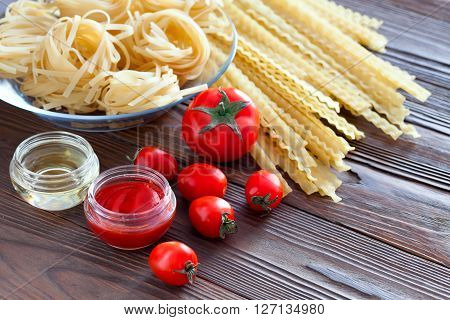 Two kinds of pasta from durum wheat and fresh tomatoes. Tomato sauce and olive oil to cook dishes. Products on a wooden table.