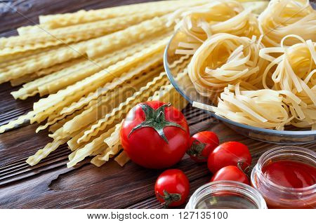 Two kinds of pasta from durum wheat and fresh tomatoes. Products on a wooden table. Tomato sauce and olive oil to cook dishes.