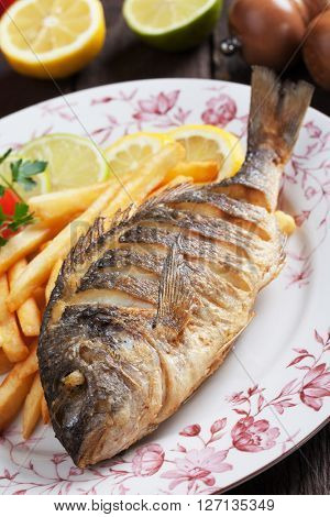 Fried bream fish with french fries and lemon