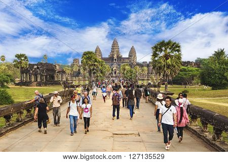 Angkor, Cambodia - December 29, 2013: Tourists at Angkor Wat temple in Siem Reap, Cambodia. Built for the Khmer Empire in the early 12th century, Angkor is the largest religious monument in the world.