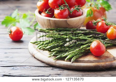 Uncooked Asparagus With Tomato On The Wooden Table