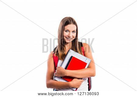 Beautiful student with schoolbag and school books. Studio shot on white background, isolated.