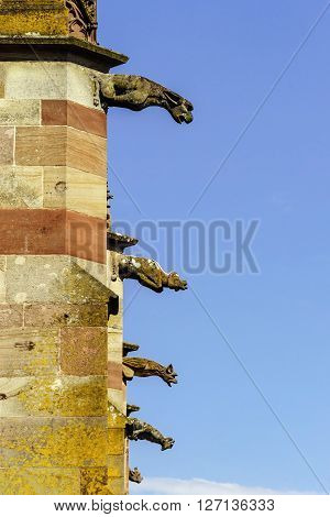 Gargoyle On A Gothic Cathedral, Detail Of A Tower On Blue Sky Background