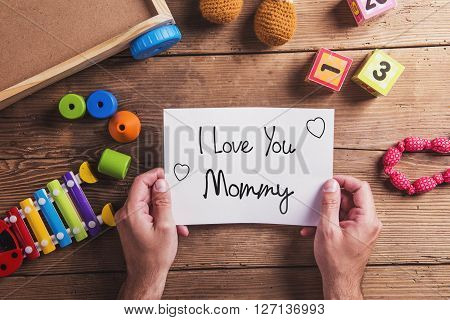 Unrecognizable hands holding I love you mommy sign. Mothers day composition. Various toys. Studio shot on wooden background.