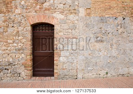 Brown door in a medieval stone and brick wall in the Tuscan village of San Gimignano Italy. Copy space to right of door if needed.