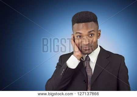 young man on blue background wearing suit and tie and wondering or thinking
