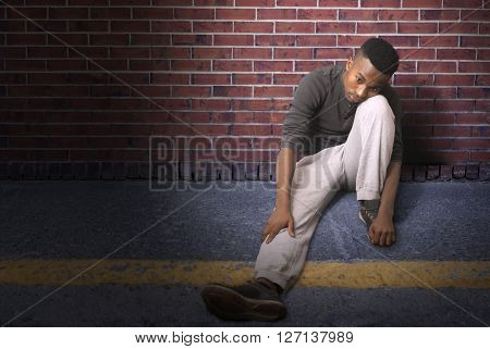 teenager seated on the pavement leaning on a brick wall at night