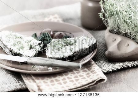 terracotta-hedgehog with home-grown garden cress and plate with brown bread and cream cheese garnished with cress lettuce and tomato on old jute sack desaturated