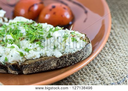 Bread with cream cheese garden cress and tomato garnish on a plate and hessian sack