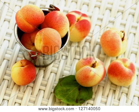 Arrangement of Ripe Fresh Apricots in Tin Bucket closeup on Wicker background. Focus on Top of Heap