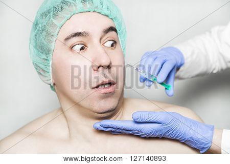 Doctor aesthetician want to make hyaluronic acid rejuvenation beauty injections to male patient in a green medical cap but patient is afraid of an injection and is looking with fear on syringe.