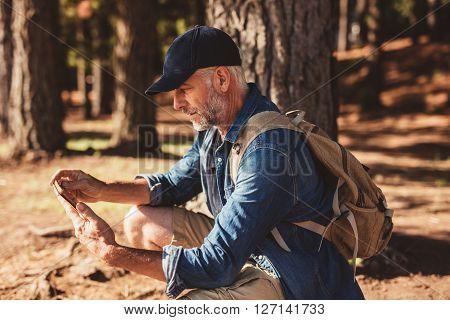 Mature Male Hiker Using Digital Tablet For Navigation