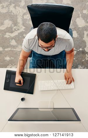 Male graphic designer using graphic tablet for design and drawing. Top view of young man working at his desk.