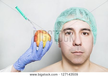 Doctor aesthetician makes hyaluronic acid rejuvenation beauty injections to a red yellow apple near male patient in medical cap. Beautician shows hyaluronic acid is healthy natural and with vitamins.